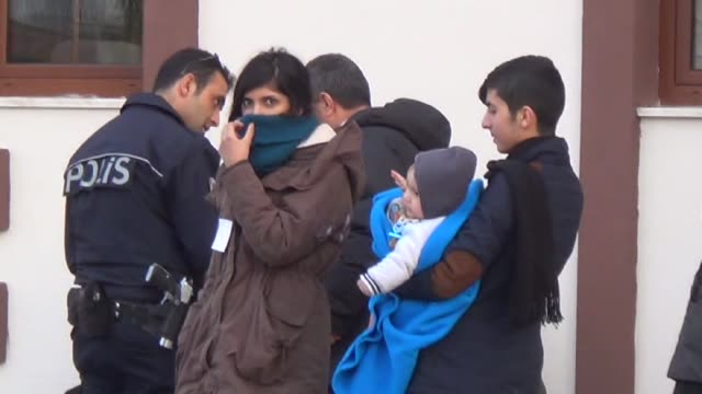 vídeos de stock e filmes b-roll de refugees are seen as they wait outside the fethiye district police department directorate after turkey 122 refugees were captured in the aegean sea... - crise de migrantes europeia 2015 2016