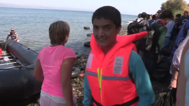 refugees are welcomed by european volunteers as they arrive greece's lesbos island on september 17, 2015. norwegian charlotte vestli and dutch lianne... - 2015 stock-videos und b-roll-filmmaterial
