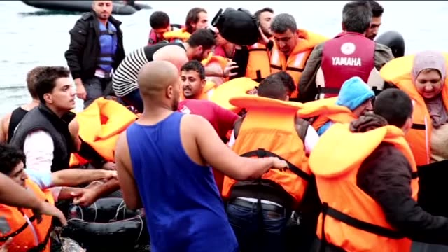 refugees arrive by a rubber boat on the greek island of lesbos after crossing the aegean sea on october 12, 2015. refugees who begin a journey with a... - 2015 stock videos & royalty-free footage