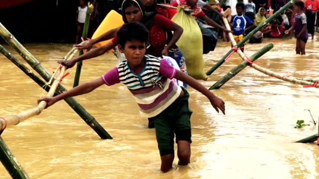 Refugees balance on bamboo as they try to cross a stream as the monsoon rains create challenges for the displaced Rohingya September 17 2017 in...