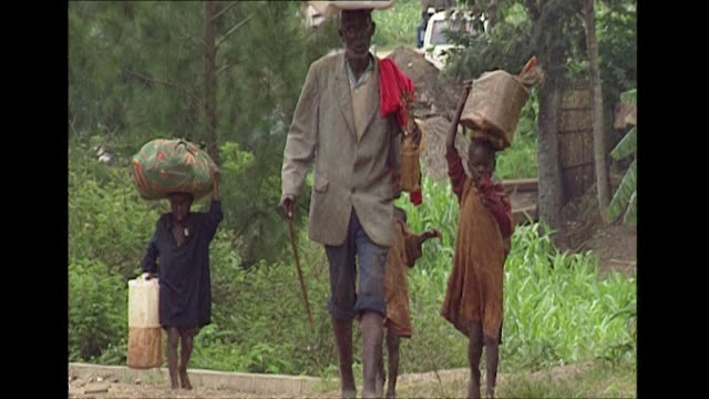 refugees carrying belongings on their heads as they walk towards border in rwanda during civil war and subsequent genocide 1994 - genocide stock videos & royalty-free footage