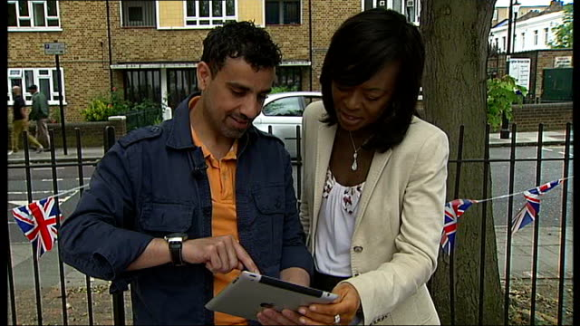 'refugees' celebrate multicultural britain for diamond jubilee reporter and emad altaay looking at ipad altaay's artwork on ipad screen people... - street party stock videos and b-roll footage