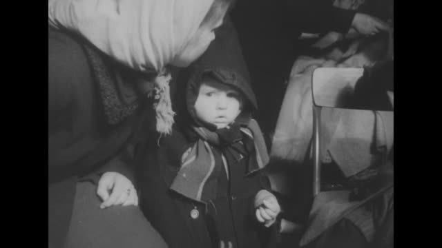 stockvideo's en b-roll-footage met refugees children / child wrapped in hooded coat and scarf with woman / elderly refugees / ls strip of muddy land with metal structures pan down to... - emigratie en immigratie