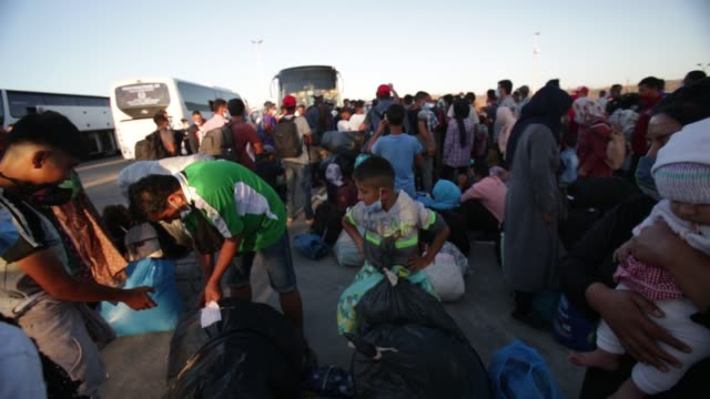 refugees children wearing protective masks to help curb the spread of coronavirus wait to board buses after their arrival at the port of lavrion... - veicolo terrestre commerciale video stock e b–roll