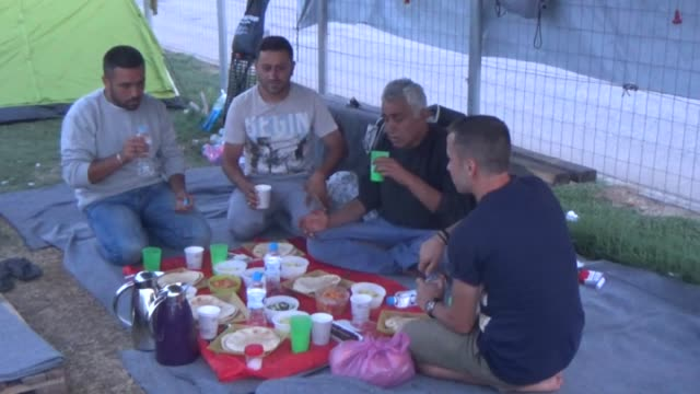 vídeos de stock e filmes b-roll de refugees cook as they wait to break their fast with the 'iftar' meal during the muslim fasting month of ramadan in the city of polikastro near the... - crise de migrantes europeia 2015 2016