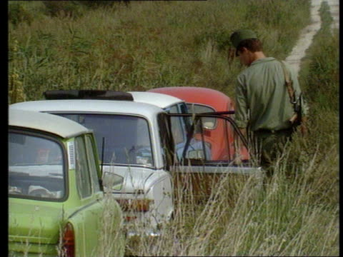 refugees enter west germany via hungary tx hungarian border guard inspecting cars abandoned by east german refugees abandoned cars with doors open - hungary stock videos & royalty-free footage