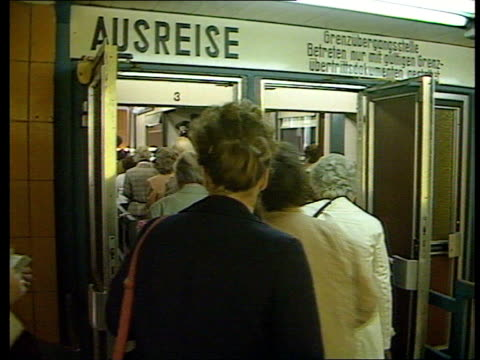 vídeos de stock e filmes b-roll de refugees enter west germany via hungary tx east germany east berlin friedrichstrasse station 'ausreise' sign pull out people going through entrance... - 1987
