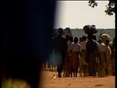 Refugees fleeing flooded areas walk down road carrying belongings Mar 00