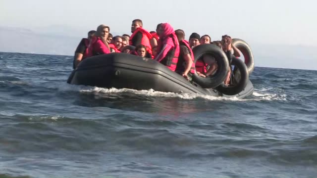 Refugees get off the boat after it arrived in Lesbos Island Greece on September 18 2015 Refugees who begin a journey with a hope to have high living...