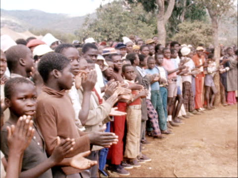 Refugees in camp ZIMBABWE Zimbabwean child refugees standing in large circle singing and clapping SOT