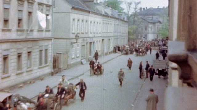 refugees in horsedrawn wagons and on foot passing through town with white sheet of surrender hanging from upper window during world war ii european... - rifugiato video stock e b–roll
