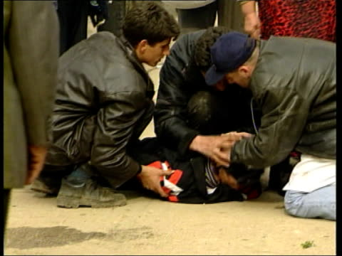 refugees; itn albania/kosovo border: ext side feet of refugees along bv track behind feet of refugees as along tms refugees towards small girl crying... - one baby boy only stock videos & royalty-free footage
