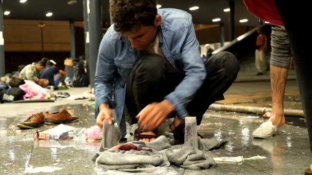 refugees lockedout of keleti station in budapest wash clothes and get drinking water from faucets in the makeshift camp that has formed around the... - 2015 stock-videos und b-roll-filmmaterial