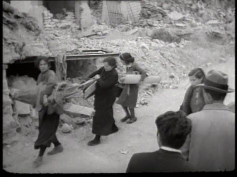 vidéos et rushes de refugees of the spanish civil war carry their belongings down a dirt road, leaving their village behind. - spain