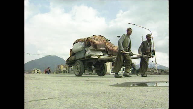 """refugees pull cart through taliban occupied kabul, afghanistan; 1997. - """"bbc news"""" stock videos & royalty-free footage"""