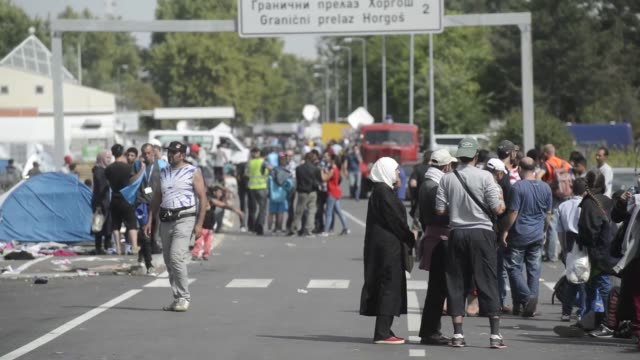 Refugees rest at the border crossing point in Horgos/Roszke on the Serbian side in Kanjiza Serbia on Thursday September 17 2015 Shots Officers gather...