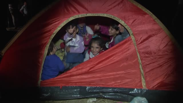 vídeos de stock, filmes e b-roll de refugees rest near the motorway after turkish gendarmerie forces stop them as they walk from istanbul to edirne on tem motorway in turkey en route to... - micrografia