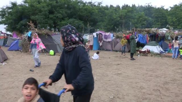 vídeos de stock e filmes b-roll de refugees seen near tents that have been erected at a informal camp besides the border fence close to the e75 horgas border crossing between serbia... - crise de migrantes europeia 2015 2016