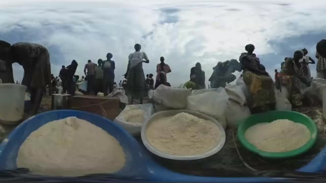 Refugees share their allocated amount of Maize Flour at a refugee settlement on February 25 2017 in Palorinya Uganda After registering their details...