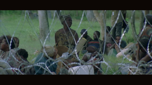 MS PAN Refugees sitting behind barbed wire fence with soldiers walking in front
