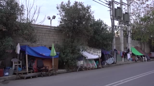 stockvideo's en b-roll-footage met refugees struggle for life under harsh conditions in athens greece on november 18 2019 afghan refugee muhammad javad speaks to reporters in front of... - athene griekenland