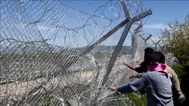 refugees stuck in the idomeni camp in greece tried to pull down the barbed wire barrier on the border with macedonia as police forces on the... - greece stock videos & royalty-free footage