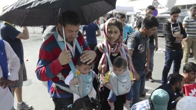 Refugees use an umbrella to shield their babies from the sun during a demonstration at the border crossing point in Horgos/Roszke on the Serbian side...