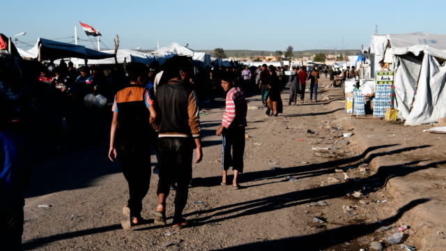 Refugees walk along a road outside Hamam alAlil refugee camp Iraqi forces backed by US and British air support have entered their sixth month of...