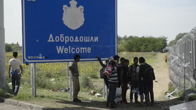 refugees walk down one side as hungarian police walk down the other side of a barb wire fence at the border crossing point in horgos/roszke on the... - traditionally hungarian stock videos & royalty-free footage