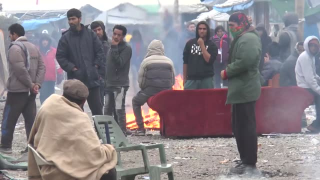 refugees warm themselves with a fire in the makeshift camp known as the jungle near calais france on october 24 2016 footag by emine urer / anadolu... - makeshift stock videos and b-roll footage