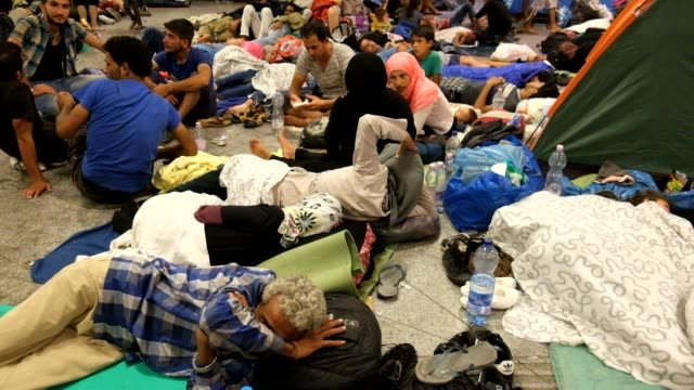 refugees who have flooded into budapest, hoping to catch trains to germany, are locked-out of keleti station in budapest. thousands have set up a... - station stock-videos und b-roll-filmmaterial