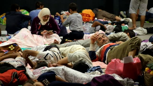 vídeos de stock, filmes e b-roll de refugees who have flooded into budapest, hoping to catch trains to germany, are locked-out of keleti station in budapest. thousands have set up a... - budapest