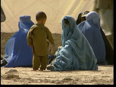 stockvideo's en b-roll-footage met refugees/relations with afghanistan itn chaman ext gv afghan refugees lined up behind barbed wire border fence pan la ms refugees looking over fence... - hoofddoek