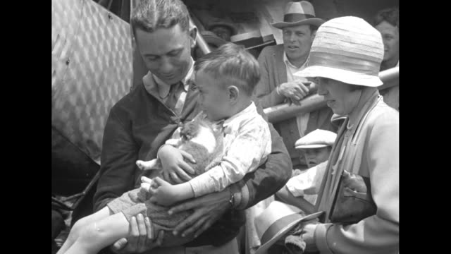 reg robbins holding a small puppy and his flight companion james kelly standing with a small boy who is robbins' son pose for photos in front of... - jumpsuit stock videos & royalty-free footage