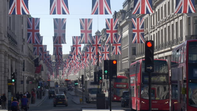regent st early morning with union jacks and red buses - bandiera del regno unito video stock e b–roll