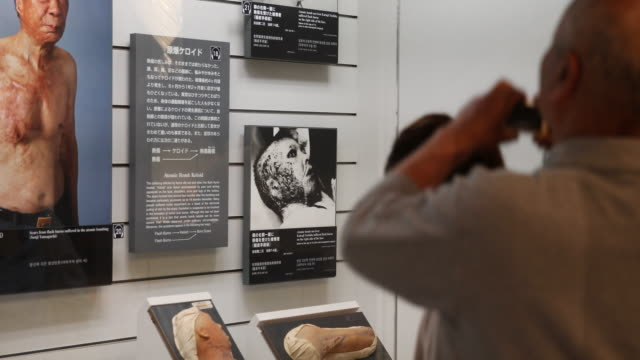 regular angle, at the atomic bomb museum nagasaki, a woman and a man are looking at a showcase that describes injuries after the disaster. a visitor... - 大量破壊兵器点の映像素材/bロール