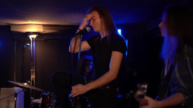 stockvideo's en b-roll-footage met repetitie van jonge rockband in muziek studii - zanger