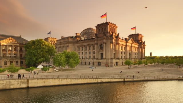 reichstag berlin with flying helicopter and summer sunset - establishing shot stock-videos und b-roll-filmmaterial