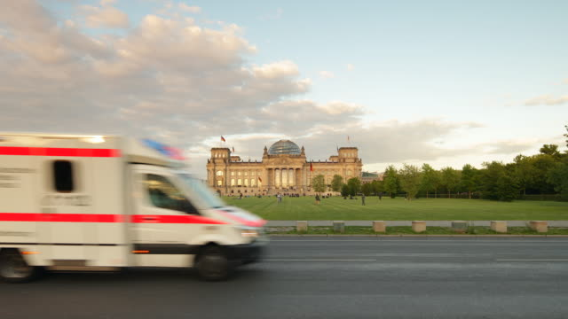 Reichstag Building in Berlin with Sun and driving Ambulance