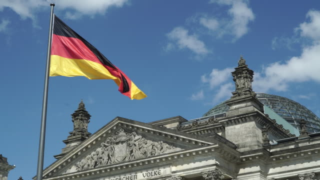 reichstag building with national flag, berlin, germany - 旗点の映像素材/bロール