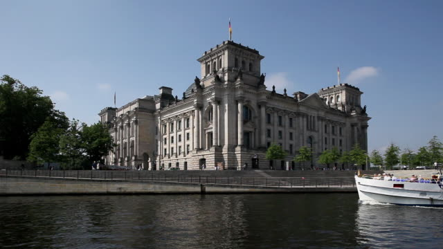 ws reichstag building with tour boat on river spree in foreground, berlin, germany - スプリー川点の映像素材/bロール
