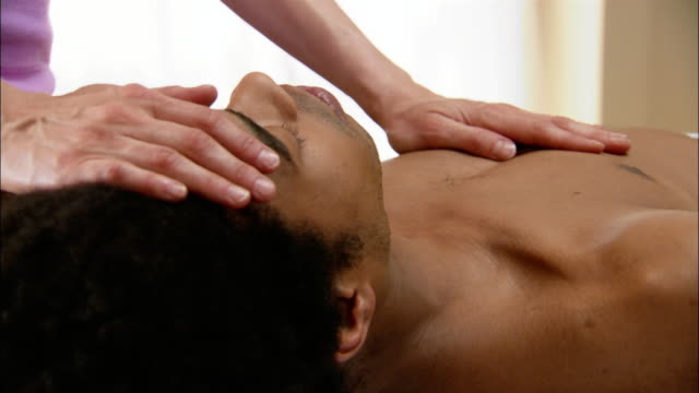 vídeos de stock e filmes b-roll de reiki practioner laying hands on man's chest, forehead and neck / zoom in to practitioner's hands on man's chest - reiki