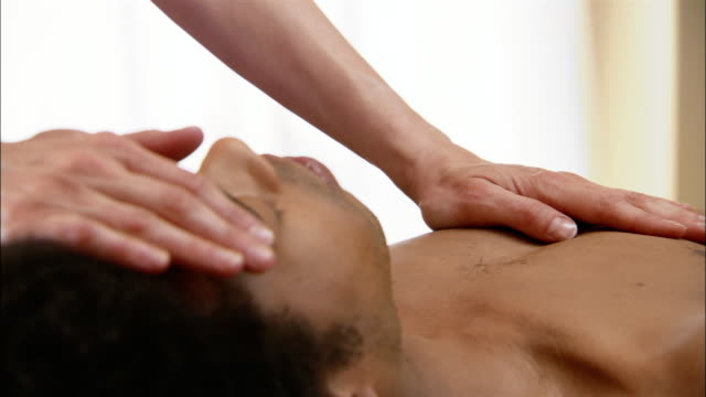 vídeos de stock e filmes b-roll de reiki practitioner laying hands on man's chest, forehead and neck - reiki