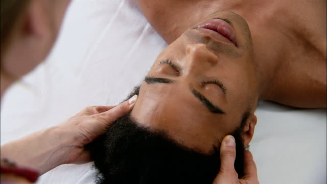 vídeos de stock e filmes b-roll de reiki practitioner laying hands on man's chest / touching man's temples - reiki