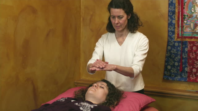 ms tu td reiki therapist raising hands above woman lying on bed  / manchester, vermont, usa - manchester vermont stock videos & royalty-free footage