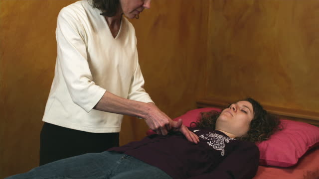 ms reiki therapist touching woman lying on bed  / manchester, vermont, usa - manchester vermont stock videos & royalty-free footage