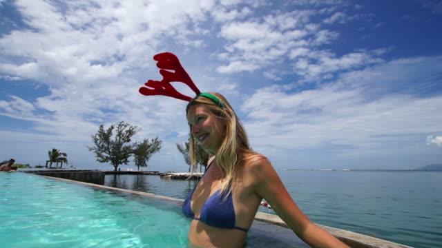 クリスマスのトナカイ耳の女性に、ポリネシアのプール