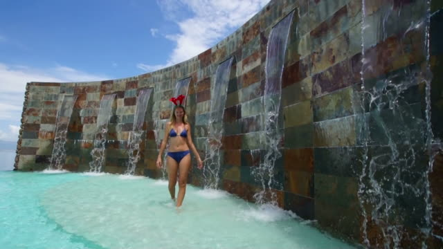 stockvideo's en b-roll-footage met reindeer ears woman for christmas in a polynesian swimming pool - haarband