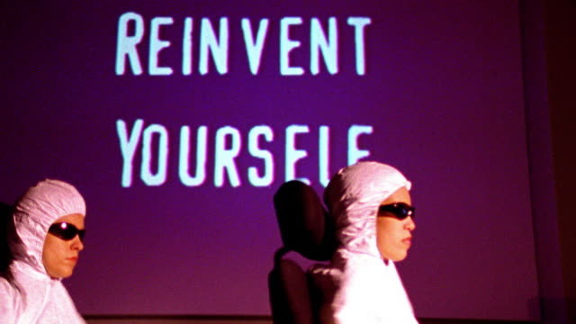 """reinvent yourself"" projected on wall in background / 2 people in hooded suits + sunglasses spin to camera - achievement stock videos & royalty-free footage"