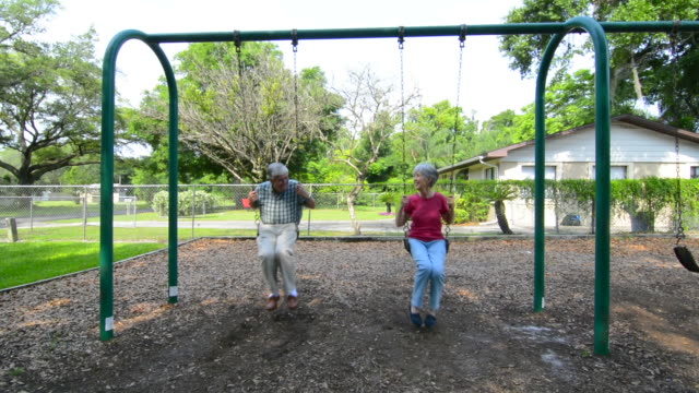 reitred couple in their 70's having fun at playground in swings laughing and playing mr- 1 mr-2 model released - swinging stock videos & royalty-free footage